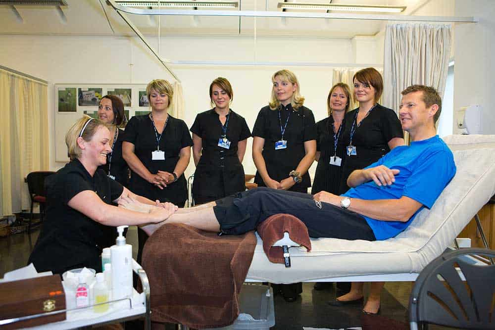 Steve Cram laying on table having his feet treated by beauty and wellbeing therapist at Bridgwater and Taunton College