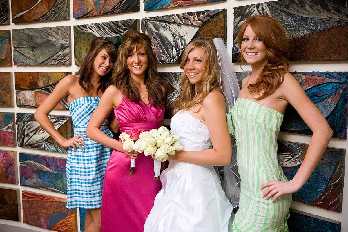 A young attractive blonde bride stands against an art piece at an art museum with her bridesmaids in California