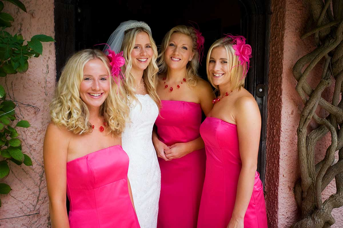An attractive young blonde bride stands in the doorway with her bridesmaids in vivid pink bridesmaid dresses
