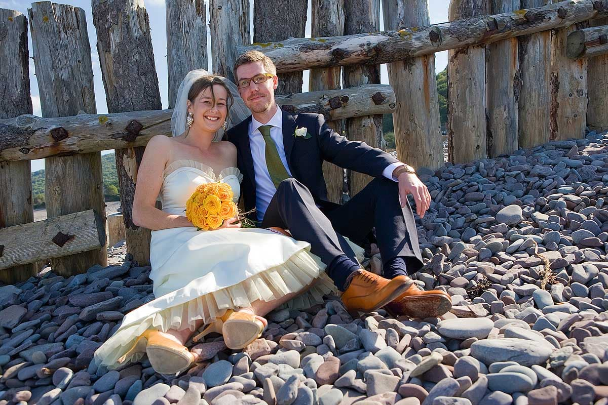 A bride and groom sit on the pebbles of the beach at Porlock Weir on their wedding day