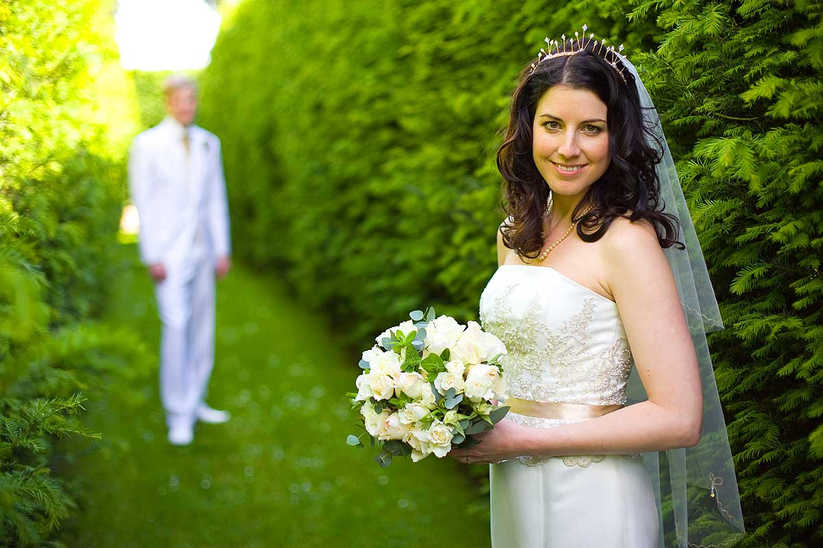 A bride stood in the foreground with her bouquet and her husband in the background at their wedding at Sheldon Manor