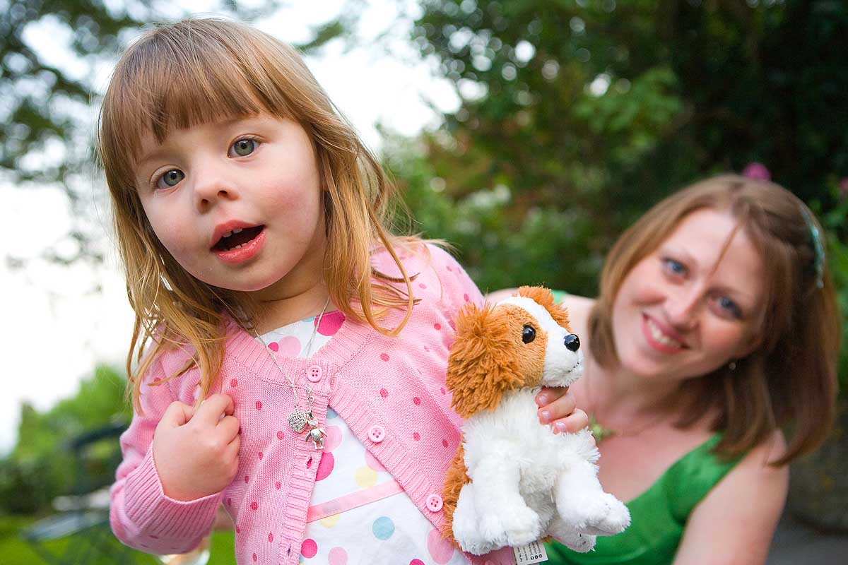 A young girl in pink with a soft toy dog looks into the camera lens at a wedding at Sheldon Manor in Chippenham