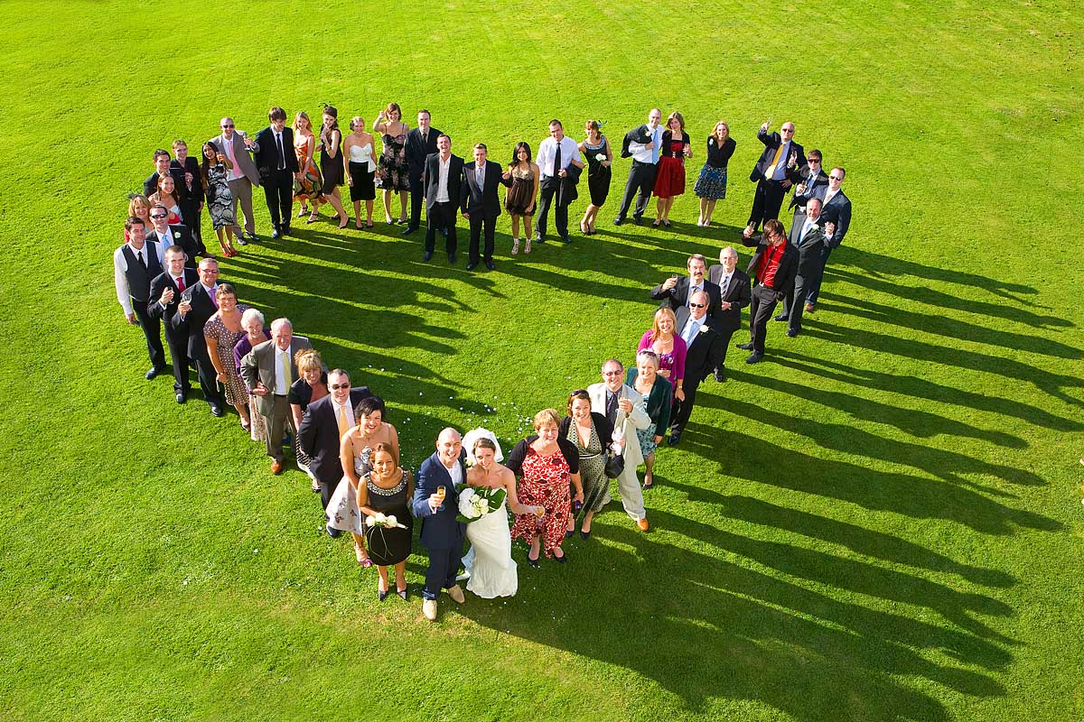 A heart shaped arrangement of wedding guests from above at Haldon Belvedere Castle in Exeter