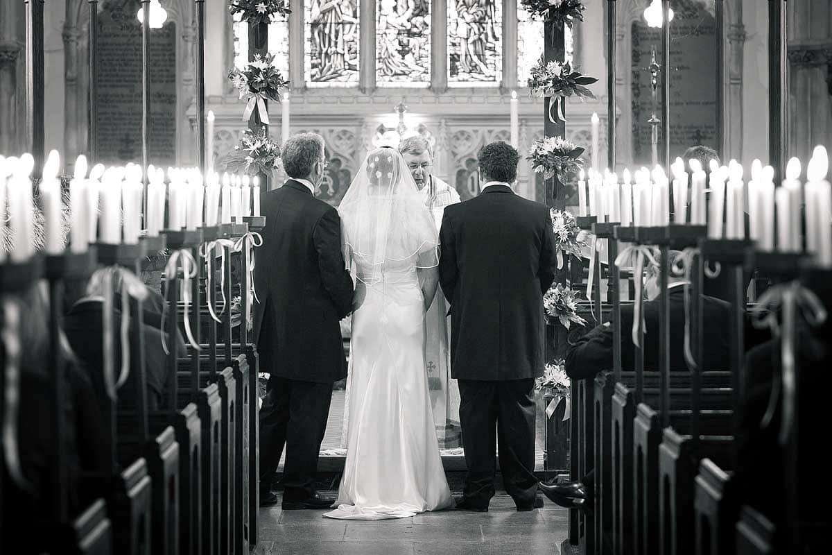 Black and white photo of a bride and groom stood during their wedding ceremony at Dulverton Church