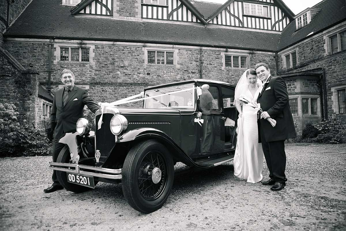 Black and white photo of a bride and groom stood outside Stoodleigh Court with a vintage car