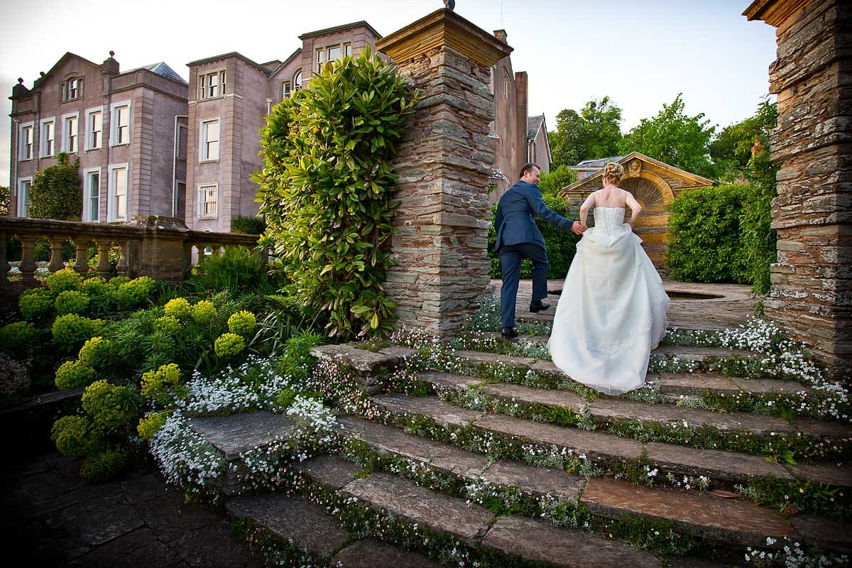 A bride and groom walking up old steps at Hestercombe Gardens in Taunton Somerset