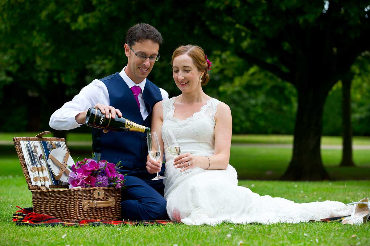 A groom pouring champagne for his wife whilst they have a picnic in Vivary Park in Taunton