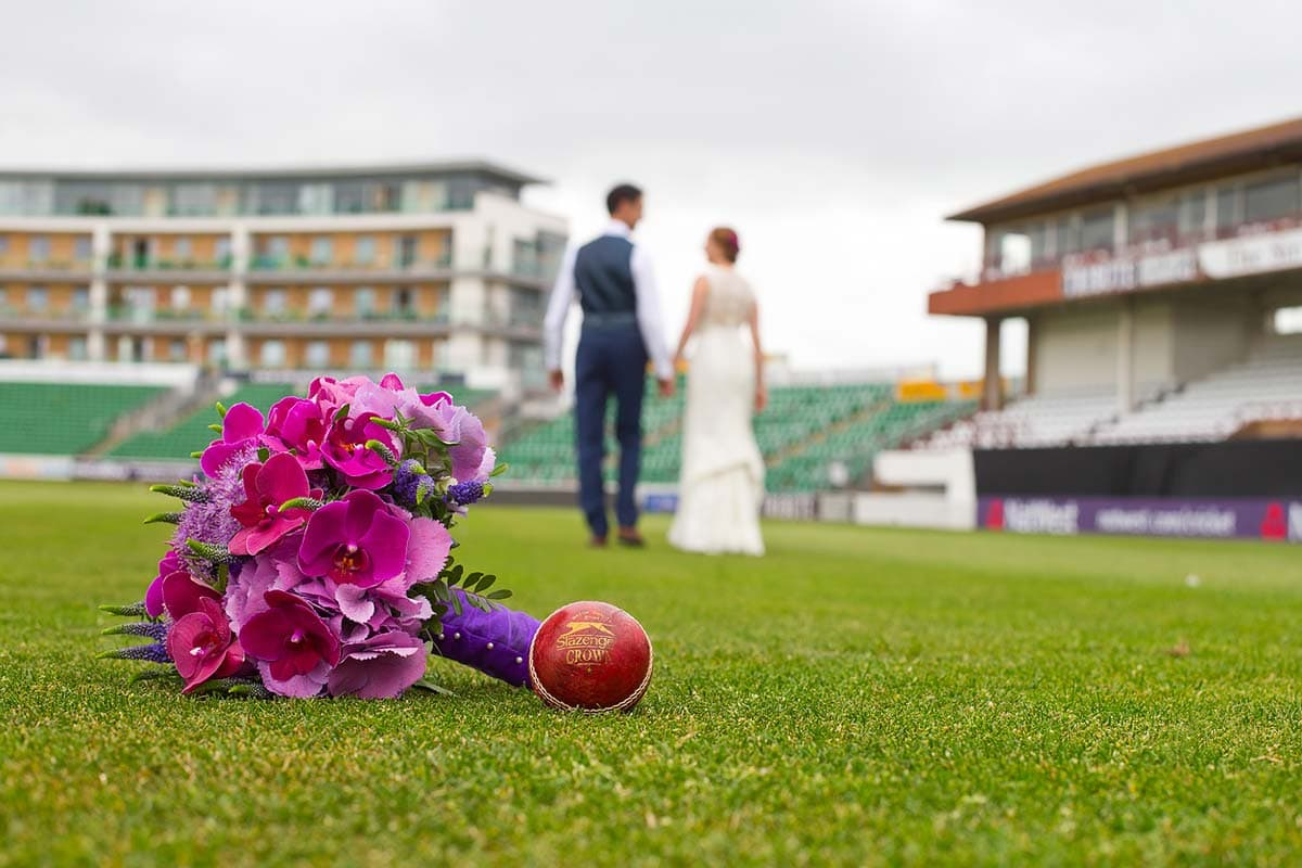Newlyweds walking away into the distance with a pink wedding bouquet in the foreground on the grass