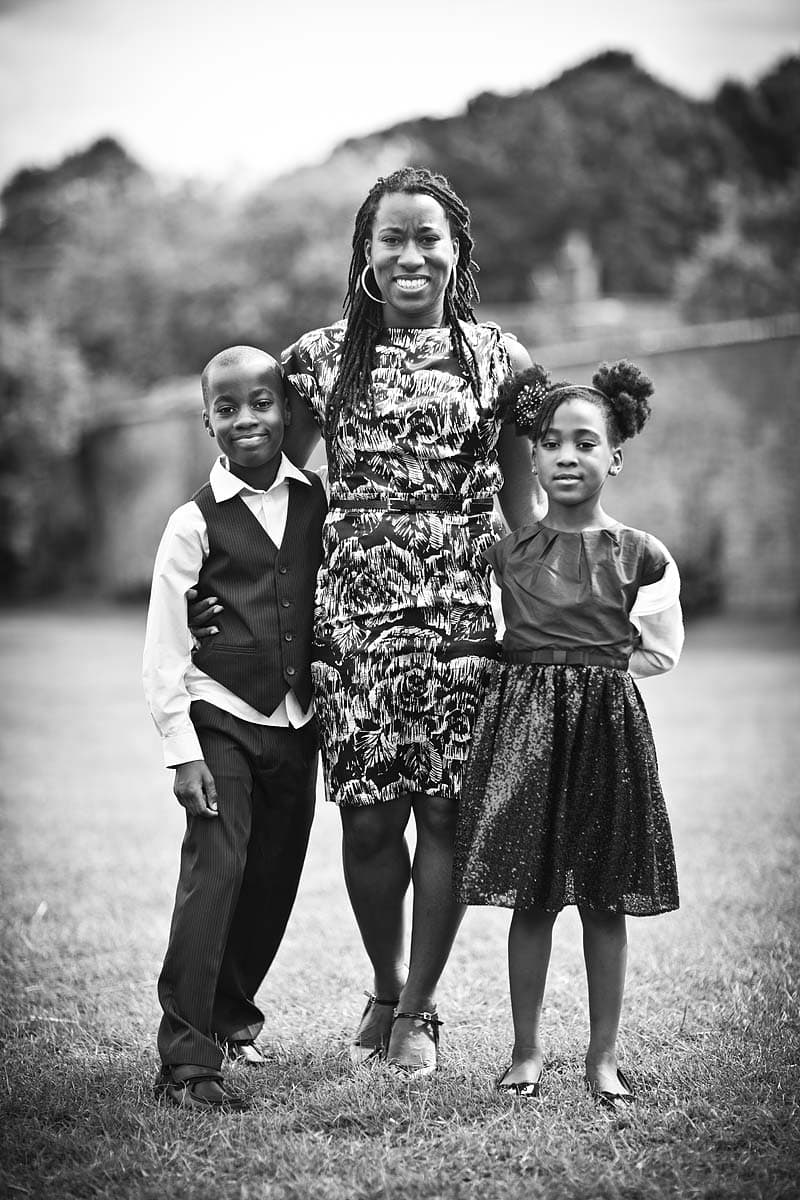 A black lady with her two children and a blurred background at a wedding in Dunster