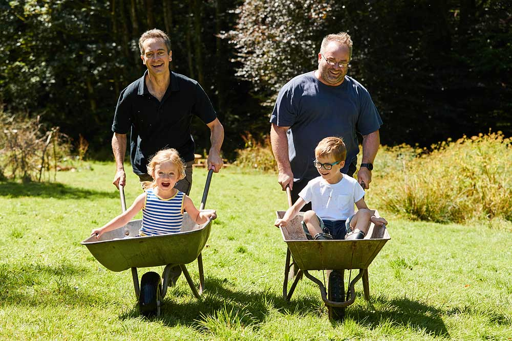 Two dads with their children in wheelbarrows having a race in Dulverton Exmoor