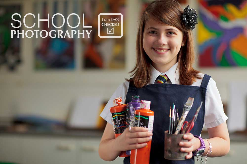 School girl holding paint pots in art class at Yeovil School
